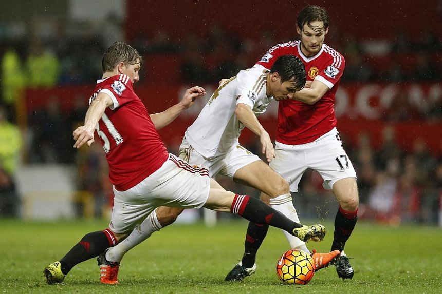 Manchester United's Daley Blind and Bastian Schweinsteiger in action with Swansea's Jack Cork.