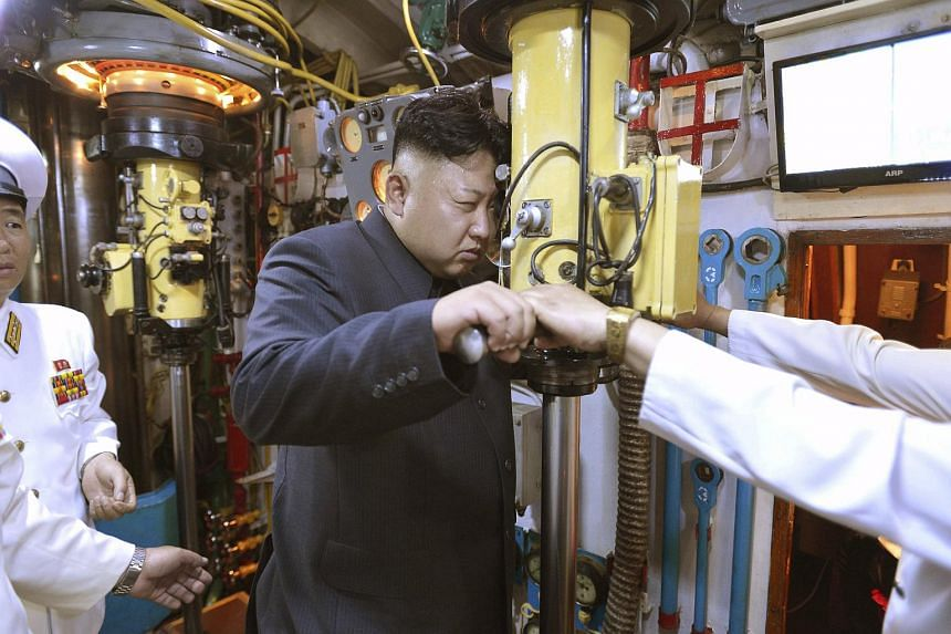 Kim Jong Un (centre) looks through a periscope of a submarine during his inspection of the Korean People's Army (KPA) Naval Unit.