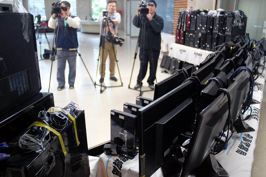Local journalists take video of confiscated computers at the Criminal Investigation Bureau in Taipei on Jan 5.