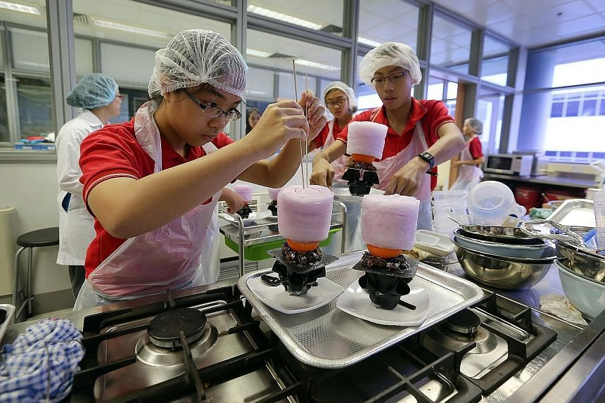 Xinmin Secondary School student Ang Yi Pin (far left), 14, places a piece of cotton candy on her team's ice-cream creation made from sweet potatoes and passion fruit. The creation - called the Metamorphic - was inspired by DC Comics superhero Metamor