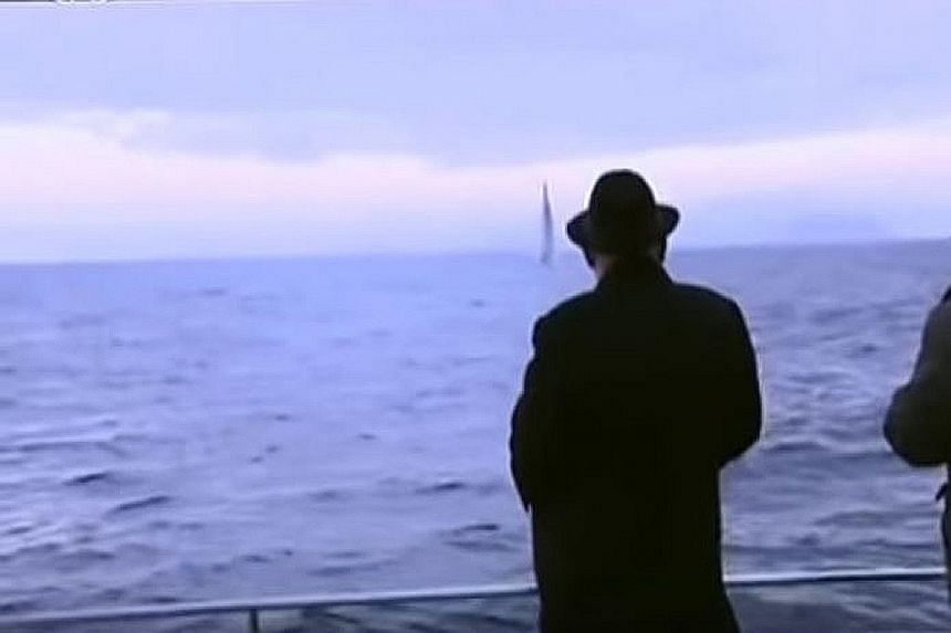 The undated video footage shows Mr Kim Jong Un on a military vessel looking on as a missile is launched vertically from underwater.
