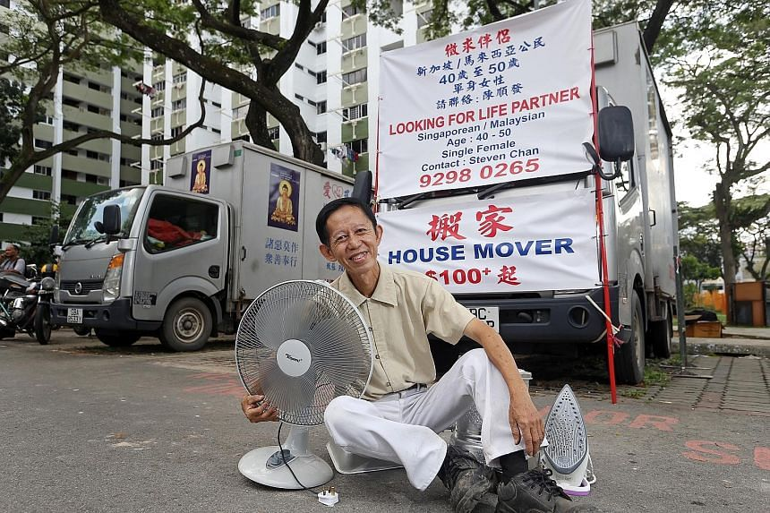 Karung guni man Steven Chan sitting in front of the advertisement banner he put up to kick start his search for love.