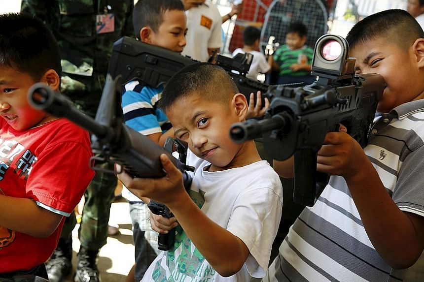 Children playing with weapons at a military facility in Bangkok during Thailand's National Children's Day celebrations yesterday. Army barracks opened their doors to youngsters, with displays of weapons and vehicles as part of the celebrations. Thail