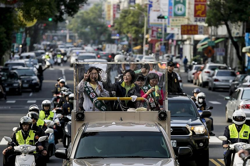 Democratic Progressive Party presidential candidate Tsai Ing-wen (centre) acknowledging supporters while on her motorcade during a campaign rally in Kaohsiung yesterday.