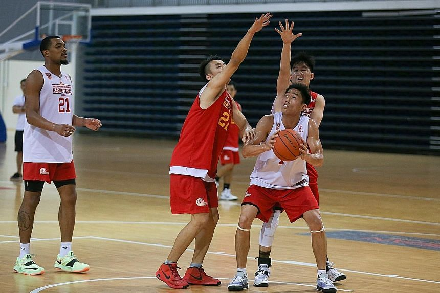 Slingers player Wu Qingde (with ball) trying to get past Kelvin Lim (on his right) and another defender during Friday's training at the OCBC Arena. American Xavier Alexander (No. 21) is one of the team's three foreigners. The Slingers play Pilipinas