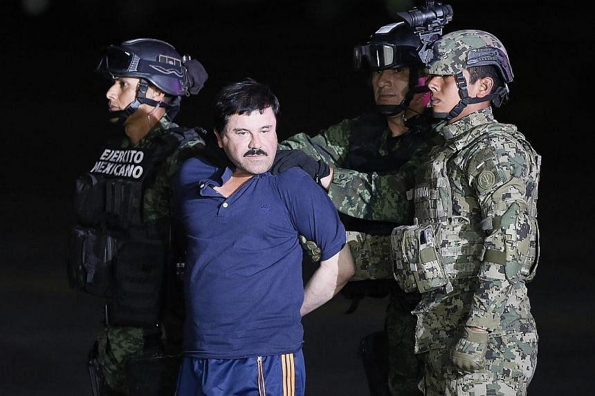 Mexican drug lord Joaquin Guzman Loera being escorted to a helicopteron Friday to be transferred to the prison in Mexico he escaped from last year.