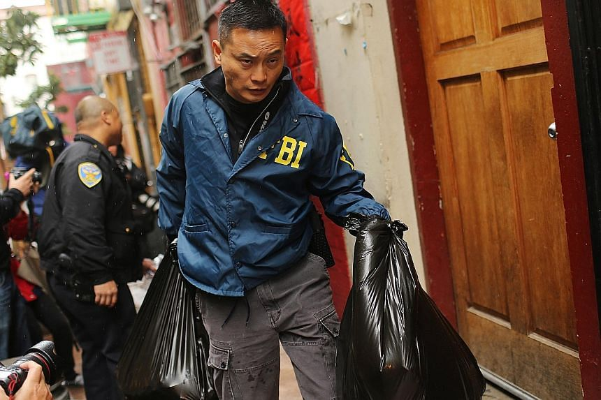 "An FBI officer removing evidence from the Ghee Kung Tong building in San Francisco's Chinatown in a raid in 2014 that netted several people including Raymond ""Shrimp Boy"" Chow."