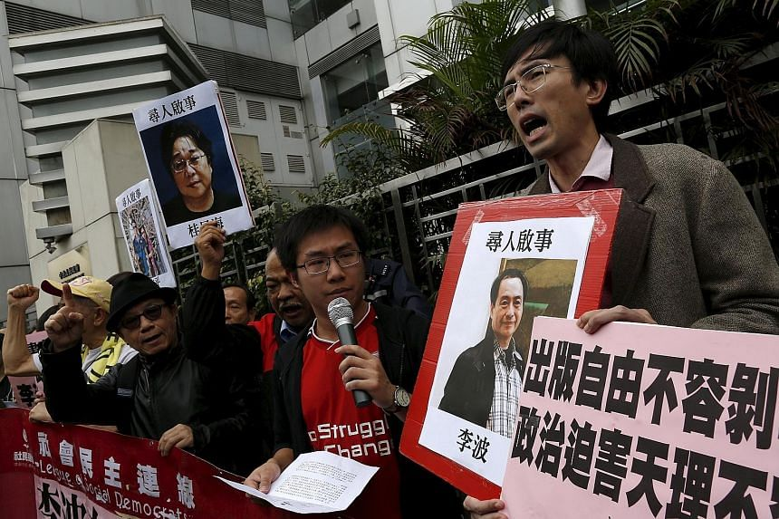 A pro-democracy demonstrator holds up a portrait of Mr Lee Bo (right) during a rally.