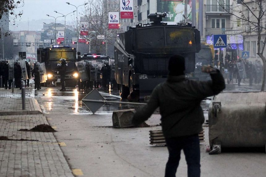 A protester throws a stone at police during clashes in Pristina.