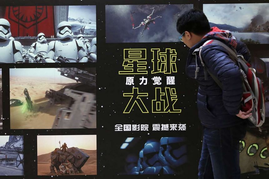 A man checks out a panel of new Star Wars posters with scenes from the movie.