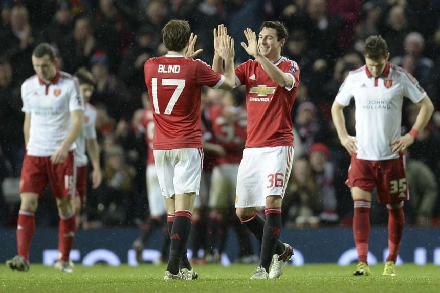 United defender Matteo Darmian (centre right) and midfielder Daley Blind celebrate Rooney's penalty goal.