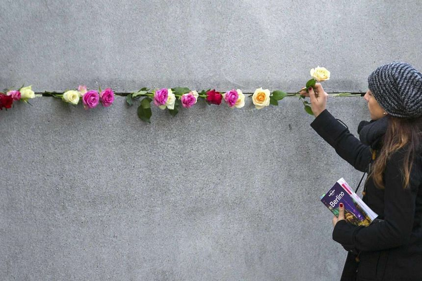 A woman places a rose at the Berlin Wall memorial in Bernauer Strasse on Nov 9, 2015.