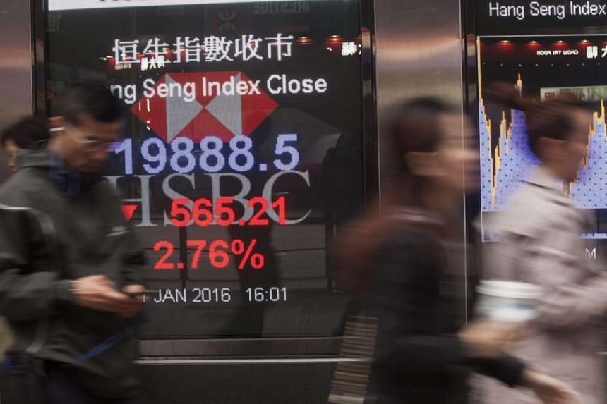 People walking past a signboard displaying the closing numbers of the Hang Seng Index, which fell 2.78 per cent, on Jan 11, 2016.