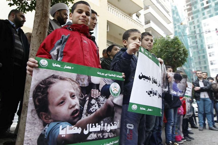 Supporters of Jemaah Islamiyah carry placards depicting pictures believed to be fore children of the Syrian town Madaya.
