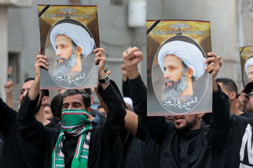 Saudi Shi'ite men hold placards bearing portraits of Muslim cleric Nimr al-Nimr during a protest in Qatif on Jan 8, 2016.