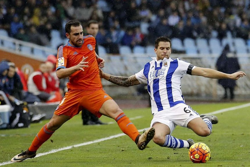 Real Sociedad's defender Inigo Martinez (right) duels for the ball with Valencia CF's striker Paco Alcacer during the Spanish Liga Primera Divison soccer match played at Anoeta stadium, in San Sebastian, northern Spain, on Jan 10, 2016.