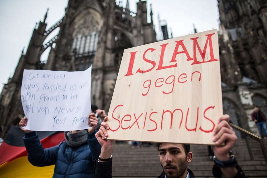 A man from Syria carries a sign that reads 'Islam against sexism' in front of the central railway station in Cologne on Jan 10, 2016.