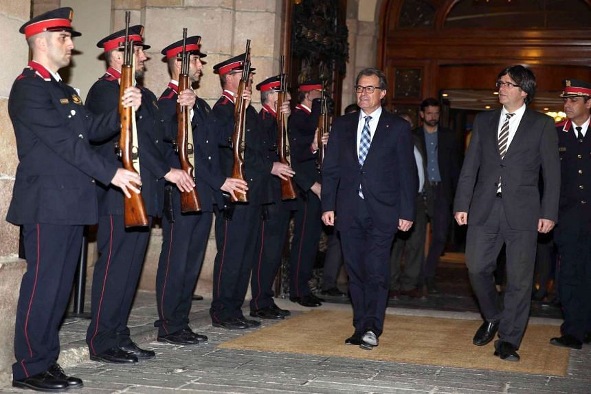 Catalonian acting President Artur Mas (centre) and Catalonian president-elect Carles Puigdemont (right) leave the regional Parliament in Barcelona, northeastern Spain, on Jan 10, 2016.