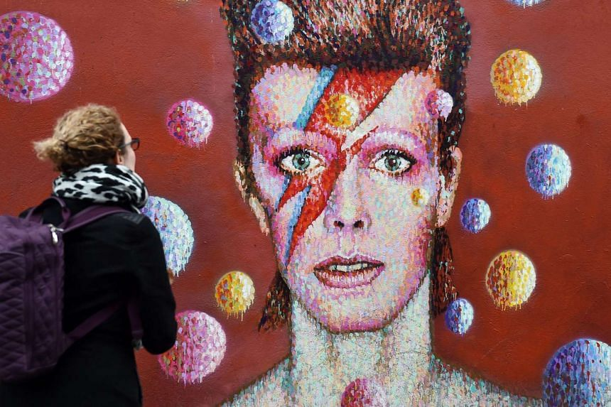 A fan of David Bowie looks over at a mural in Brixton, London on Jan 11, 2016.