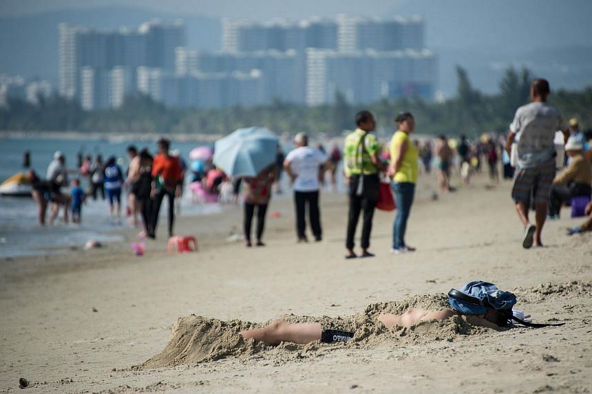 A man covered with sand, enjoying the sun on a beach in Sanya, Hainan on Dec 18, 2015.