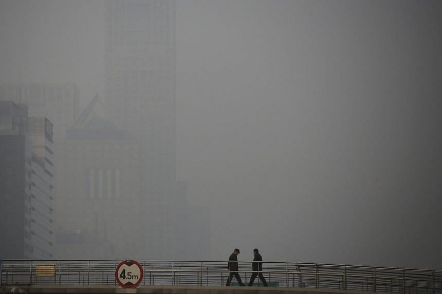 People walking on a pedestrian bridge on a heavily polluted day in Beijing, China on Jan 3.