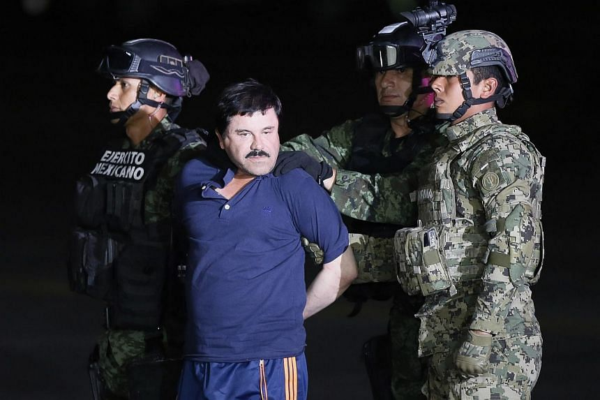 Alleged fugitive Mexican drug lord Joaquin 'El Chapo' Guzman is escorted by the authorities to a Mexican Army helicopter in Los Mochis, Mexico on Jan 8.