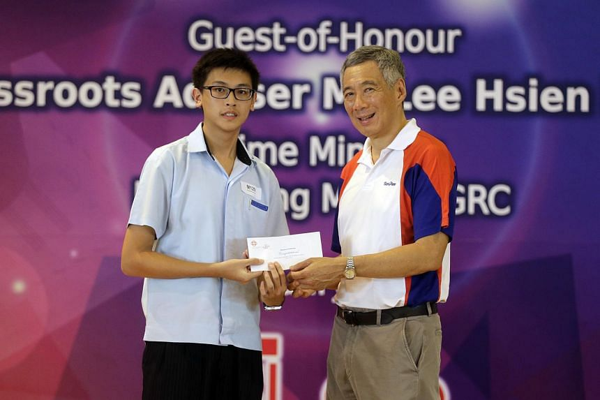PM Lee presenting the Edusave scholarship to Ryan Sen Rajagopal during the Teck Ghee CCC Bursary Awards Presentation Ceremony in Townsville Primary School on Jan 10.