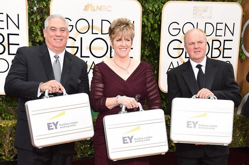Representatives of Ernst & Young carrying suitcases filled with names of the Golden Globe winners.