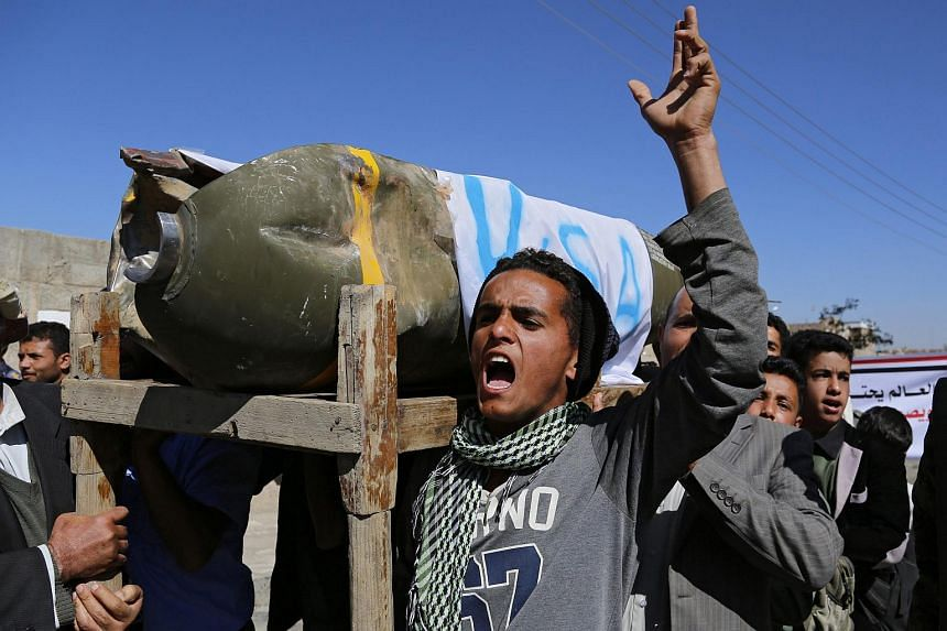 Yemenis shout anti-Saudi slogans and carry the remains of what appears to be a US-made cluster bomb allegedly dropped during Saudi-led airstrikes on Jan 10.