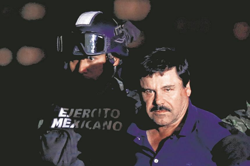 """Joaquin """"El Chapo"""" Guzman is escorted by soldiers during a presentation at the hangar in Mexico City."""