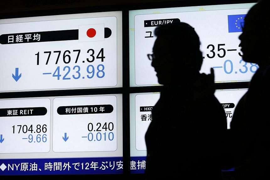 Pedestrians walk past an electronic stock board displaying the Nikkei 225 Stock Average outside a securities firm in Tokyo.