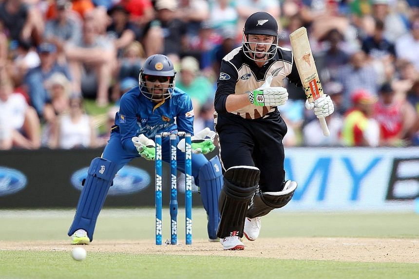 New Zealand's Colin Munro running between the wickets during the first T20 match as Sri Lanka's Dinesh Chandimal watches.
