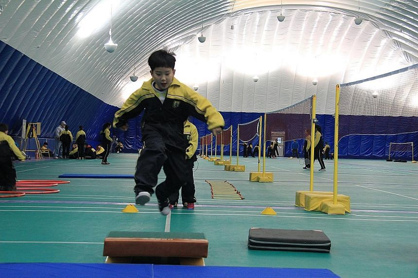 Pupils exercising under an inflatable dome at Beijing Huijia Private School. Standing three storeys high, the 3,000 sq m dome filters out harmful particles, maintaining an air quality index of less than 30. At least five institutions in Beijing now p