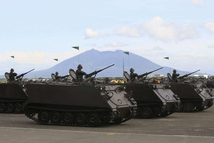 A column of tracked armoured vehicles roll by in a parade marking the 80th anniversary of the founding of the Armed Forces of the Philippines at Clark Air Base on Dec 21, 2015.
