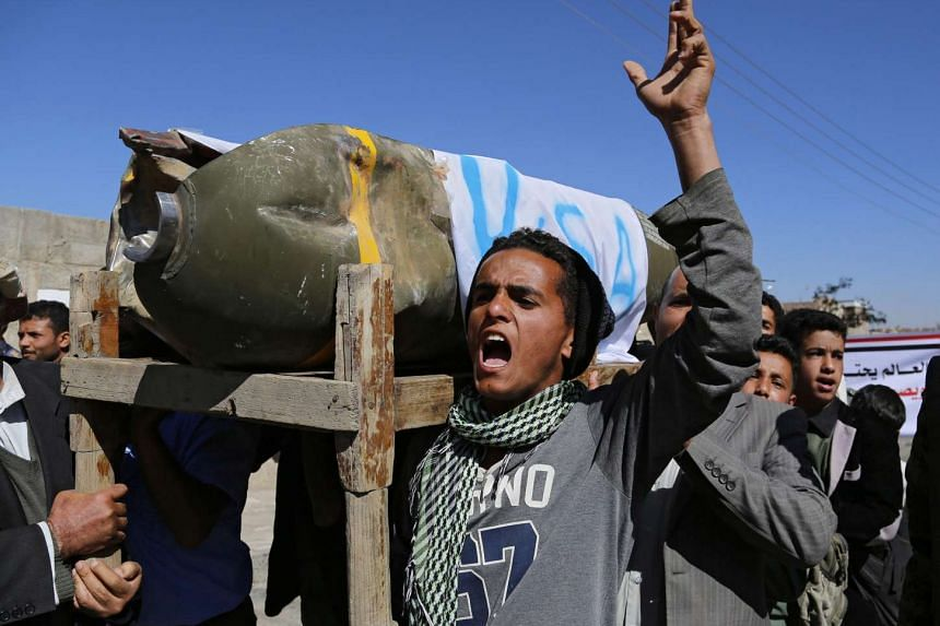 Yemenis shout anti-Saudi slogans and carry the remains of what appears to a US-made cluster bomb allegedly dropped during Saudi-led airstrikes, during a protest outside the UN offices in Sana'a, Yemen on Sunday.