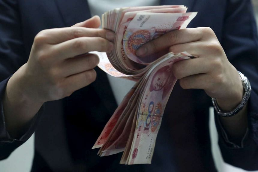A clerk counts Chinese 100 yuan banknotes at a branch of a foreign bank in Beijing.