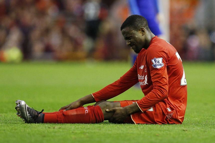 Liverpool's Divock Origi sits injured before being substituted during the match against Leicester City.