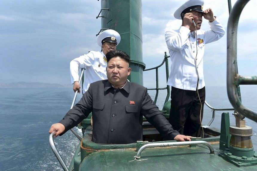North Korean leader Kim Jong Un (centre) inspecting a submarine in this undated photo released by the Korean Central News Agency on June 16, 2014.