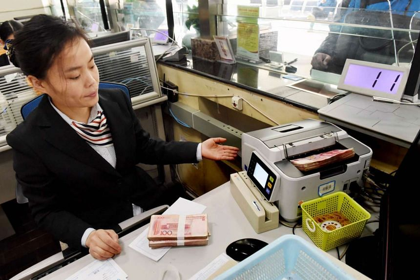 An employee counting 100-yuan notes at a bank in Lianyungang on Jan 7.