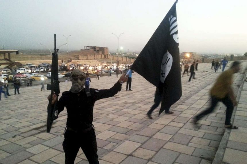 An ISIS militant holding a flag and a weapon in the city of Mosul, Iraq on June 23, 2014.