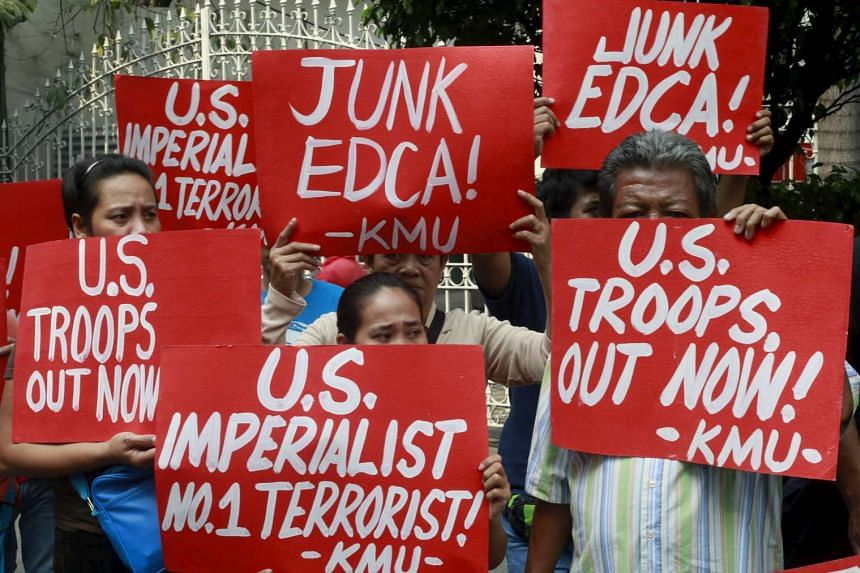 Activists hold placards denouncing the Enhanced Defense Cooperation Agreement outside the Supreme Court in Manila on Jan 12, 2016.