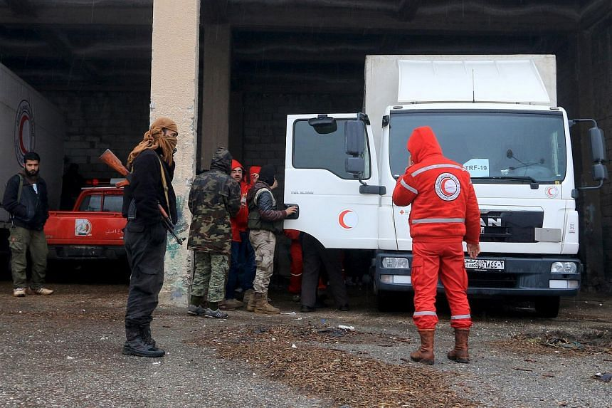 Rebel fighters inspecting Red Crescent vehicles on their way to Al Foua and Kefraya, in Idlib province, Syria on Jan 11, 2016.