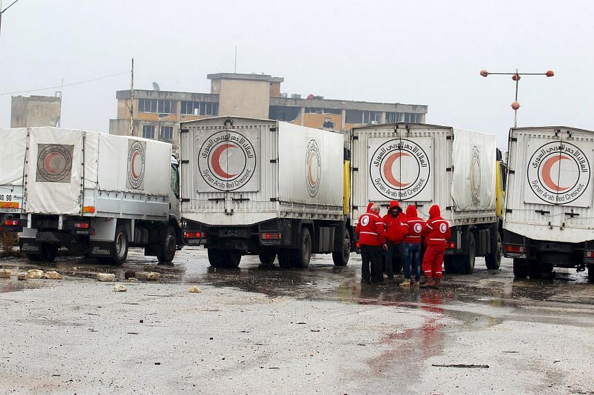 Red Crescent workers standing near their vehicles prior to inspection from rebels before heading to Al Foua and Kefraya, in Idlib province, Syria on Jan 11, 2016.