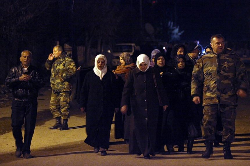 Syrians from the besieged town of Madaya walking near Syrian soldiers as they leave towards the capital for treatment, on Jan 11, 2016.