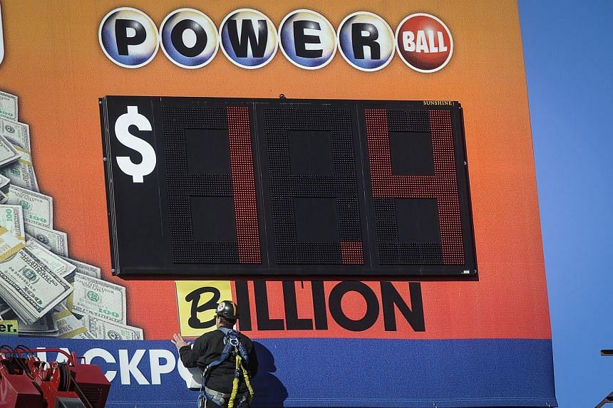 A worker changing the word million to billion, indicating the new jackpot amount for the multi-state Powerball lottery.