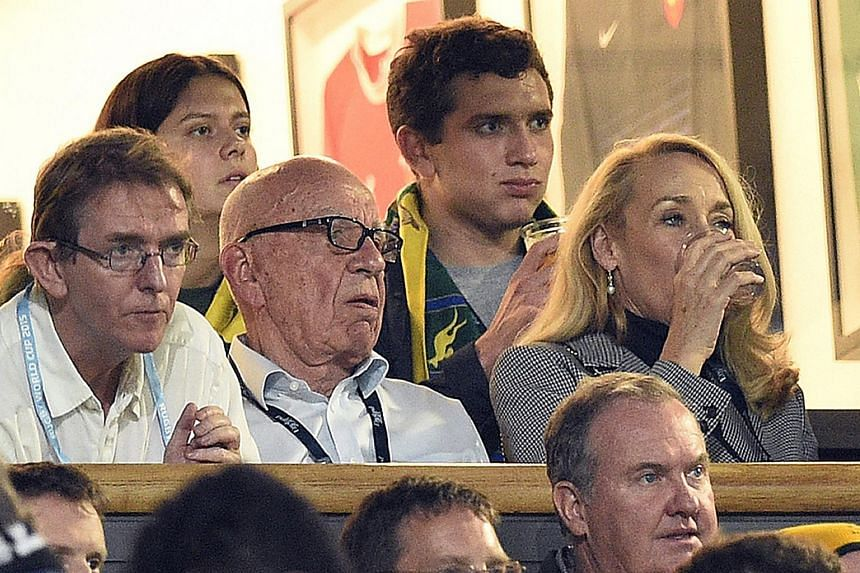 Media magnate Rupert Murdoch (centre) and former model Jerry Hall (right) watching the 2015 Rugby World Cup finals between New Zealand and Australia, in London on Oct 31, 2015.