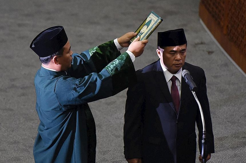 Mr Ade (right), a Golkar Party MP, being sworn in as the new Speaker of Indonesia's Parliament in Jakarta yesterday.