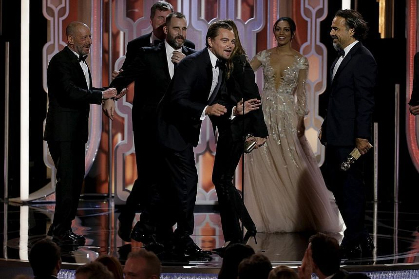 The Revenant star Leonardo DiCaprio (above, at the microphone) celebrating the film's win for Best Motion Picture, Drama with crew members including director Alejandro Gonzalez Inarritu (far right).