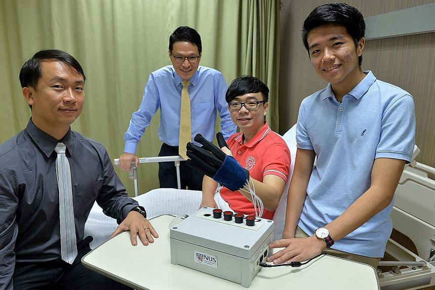 Far left: The team from NUS' biomedical engineering unit include (from left) Prof Yeow, Assistant Professor Lim Jeong Hoon, Mr Yap Hong Kai and Mr Benjamin Ang Wee Keong Left: Mr Yap demonstrating how the robotic glove helps patients to carry out reh