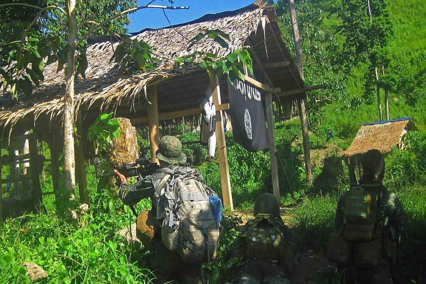Philippine marines raiding the camp of a gang that had pledged allegiance to ISIS in Palimbang town, Sultan Kudarat province, Mindanao, last November. Weapons and ISIS flags were recovered following a firefight.